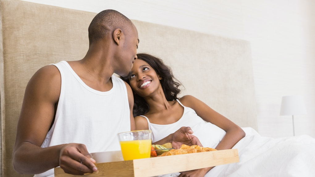 Young man serving breakfast to woman in the bed