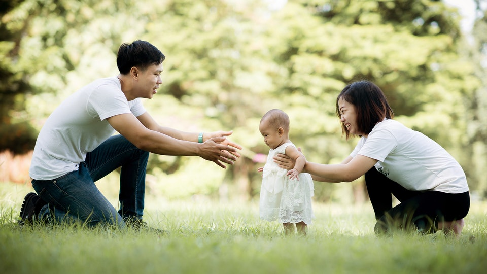 Happy young family spending time together outside, baby walking on the grass