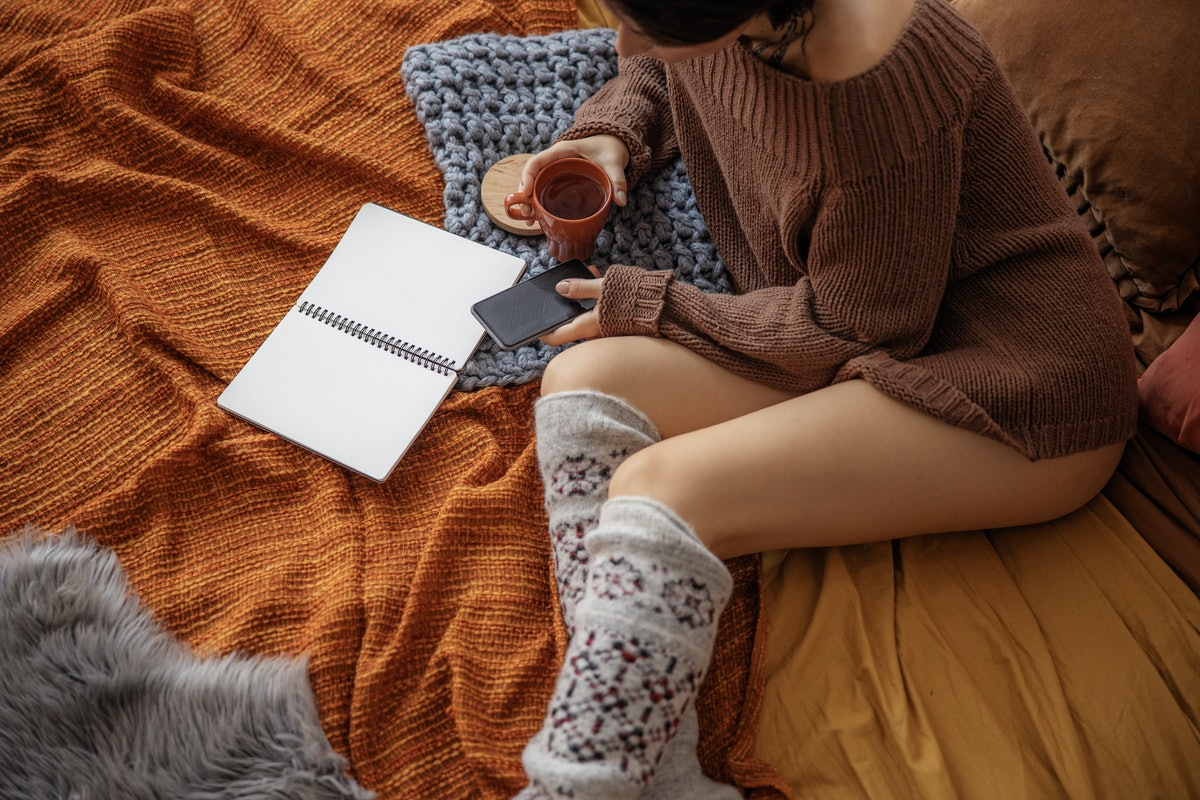 Top view of woman with hot drink and mobile phone stock photo