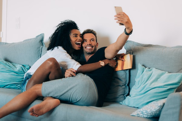 A young couple takes a selfie on their phone while sitting on the couch.