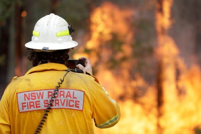 A firefighter uses his phone to record a controlled burn near Tomerong, Australia, in an effort to c...