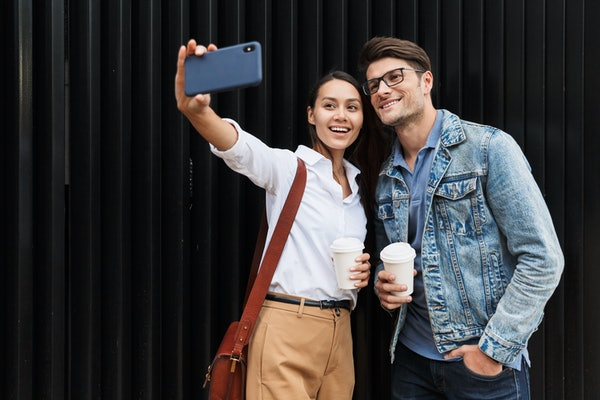 A stylish couple takes a selfie on a phone while out in the city for a coffee date.