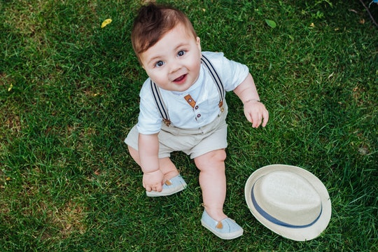 Top view of beautiful baby boy sitting on the grass dressed in a vintage look and looking at the cam...