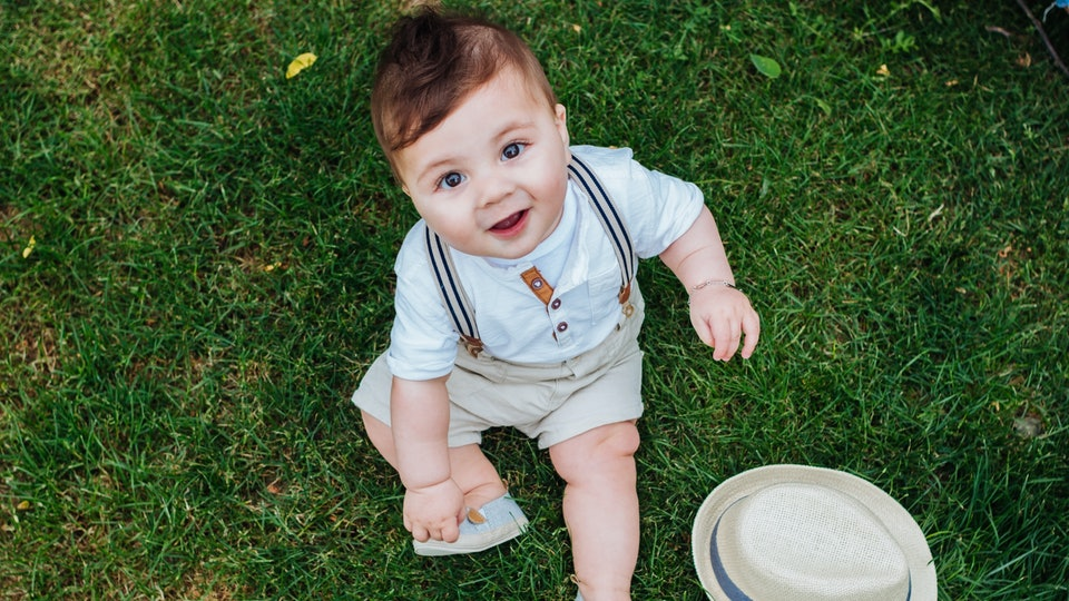 Top view of beautiful baby boy sitting on the grass dressed in a vintage look and looking at the camera