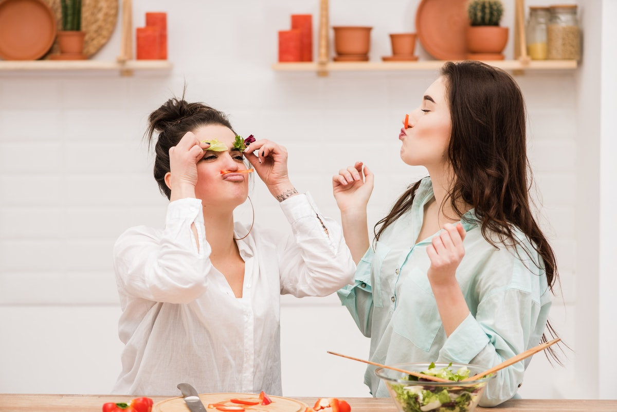 Happy lesbian couple with vegetable in kitchen.