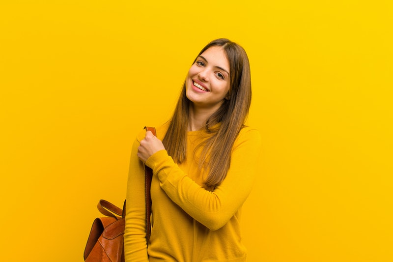 young pretty woman feeling happy, positive and successful, motivated when facing a challenge or celebrating good results against orange background