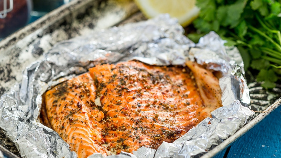 Tasty Baked Fish Salmon in Foil on Blue Table, Close-up