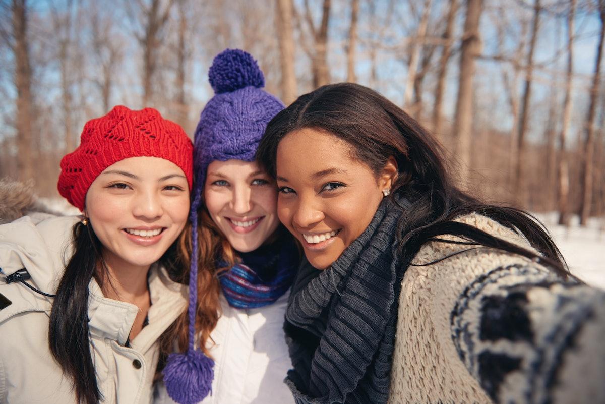Group of girl friends enjoying taking selfies in the snow in winter