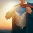 superhero businessman looking at city skyline at sunset. the concept of success, leadership and vict...
