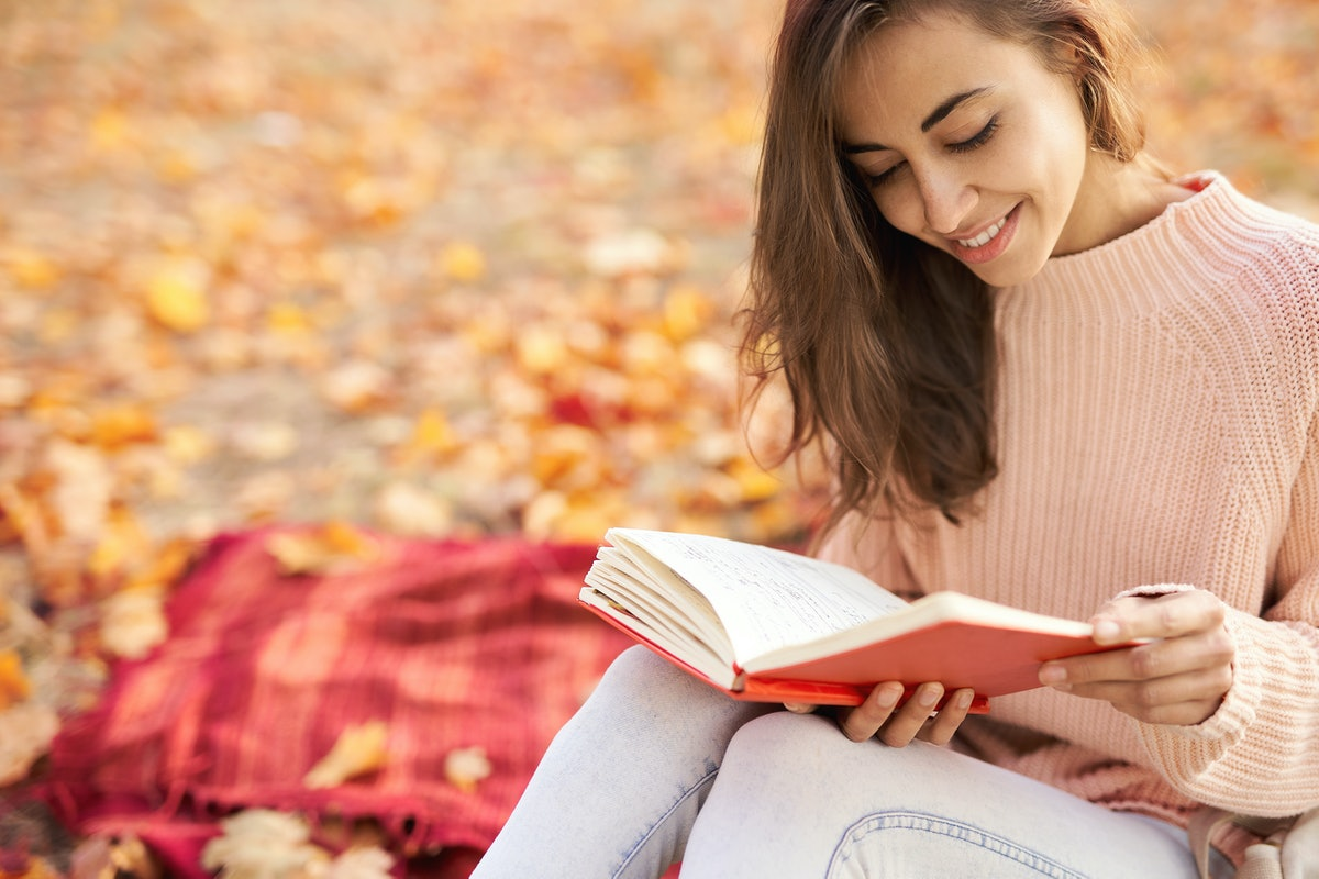 Close up portrait of cute smiling woman woman in autumn park with fall colorful background, sitting on blanket, reading a diary, enjoying warm sunny weather. Fall season concept. Outdoor lifestyle