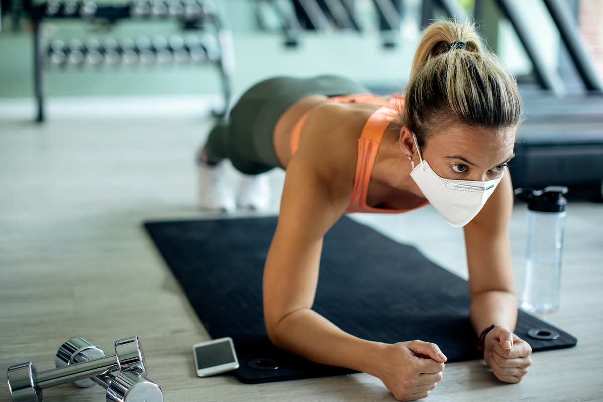 A person wears a white mask while holding a forearm plank in the gym. Walk outs give your entire body a good dynamic stretch and muscle activation.
