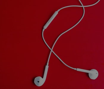 White earpods on a red background