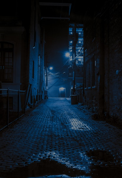 Dark and scary vintage cobblestone brick city alley at night in Chicago