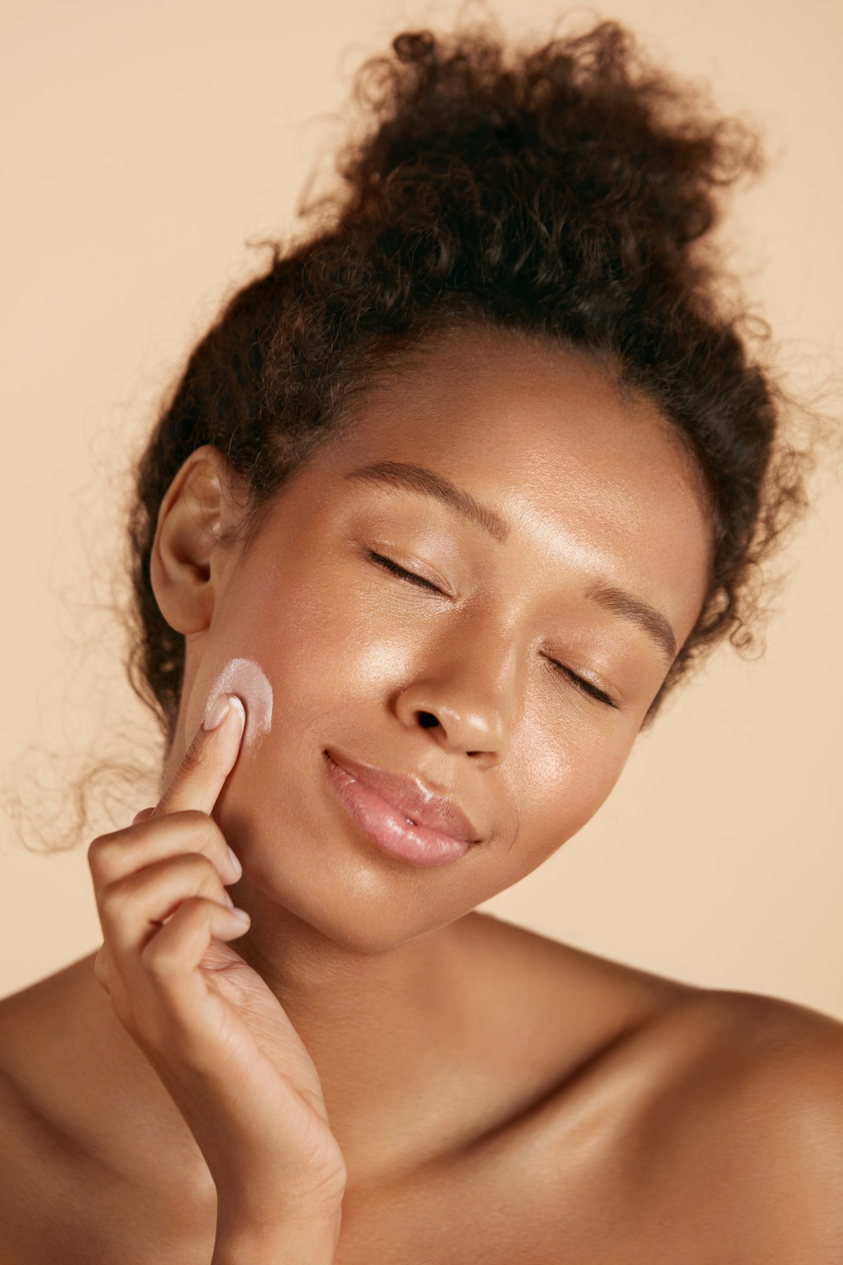 Face skin care. Woman applying cosmetic cream on clean hydrated skin portrait. Beautiful happy smili...