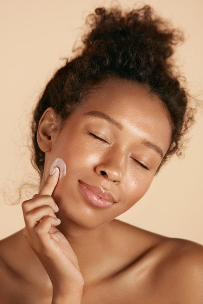 Face skin care. Woman applying cosmetic cream on clean hydrated skin portrait. Beautiful happy smiling african americangirl model with natural makeup applying facial moisturizer, beauty product