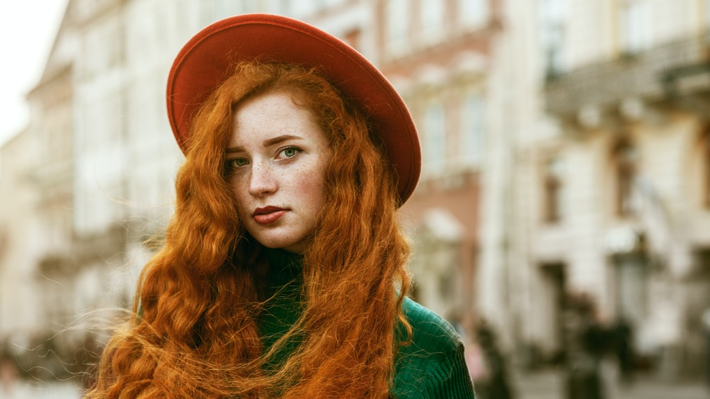 Close up portrait of young beautiful fashionable redhead woman with freckles, very long curly hair, wearing green turtleneck, orange hat, posing in street of european city. Copy, emty space for text