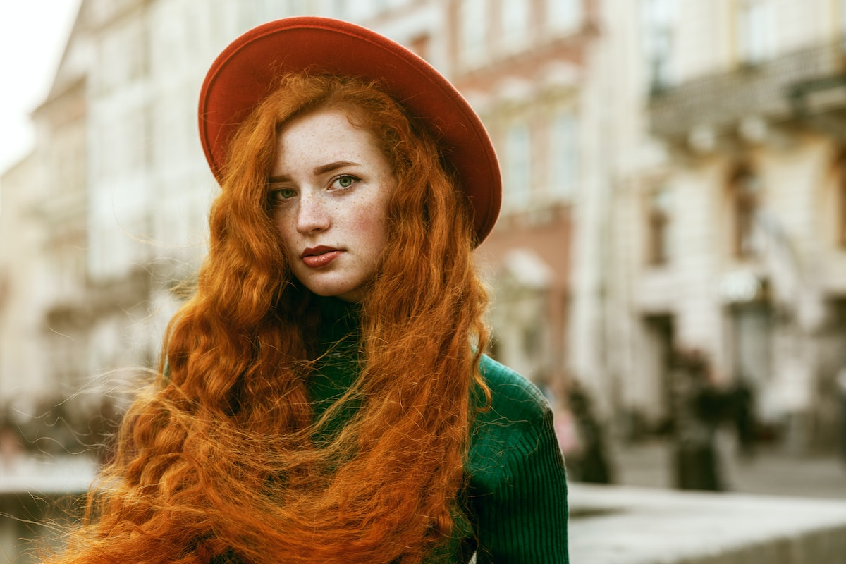 Close up portrait of young beautiful fashionable redhead woman with freckles, very long curly hair, ...