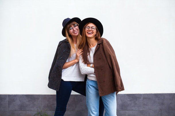 Image of two young happy women friends standing over white wall. Looking at camera.Outdoor portrait of long-haired young woman in hat and jackets hanging out with best friend in sunny day.Copy space.