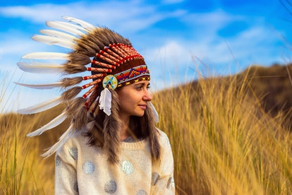 Beautiful young woman in black dotted white chief style Native American headdress during sunset
