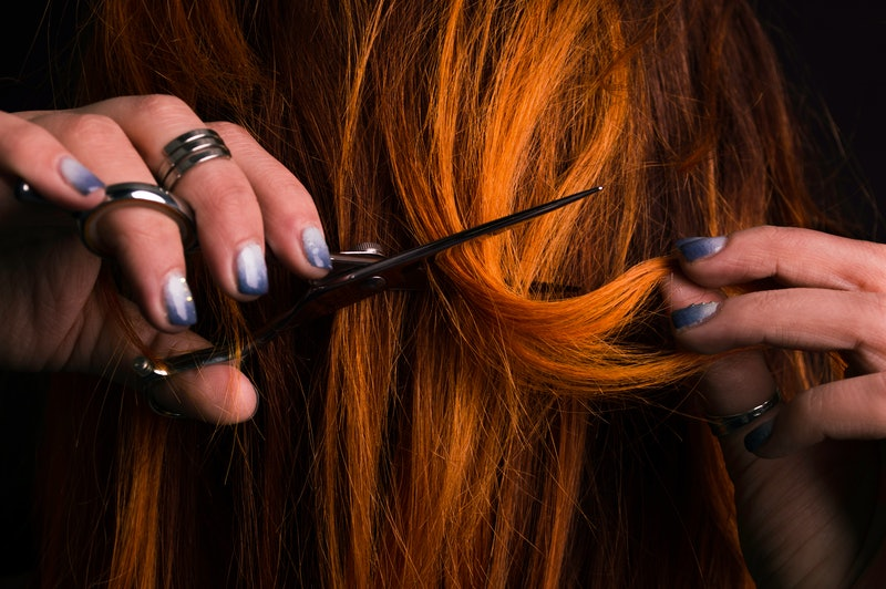 Ginger female haidresser cutting her own hair