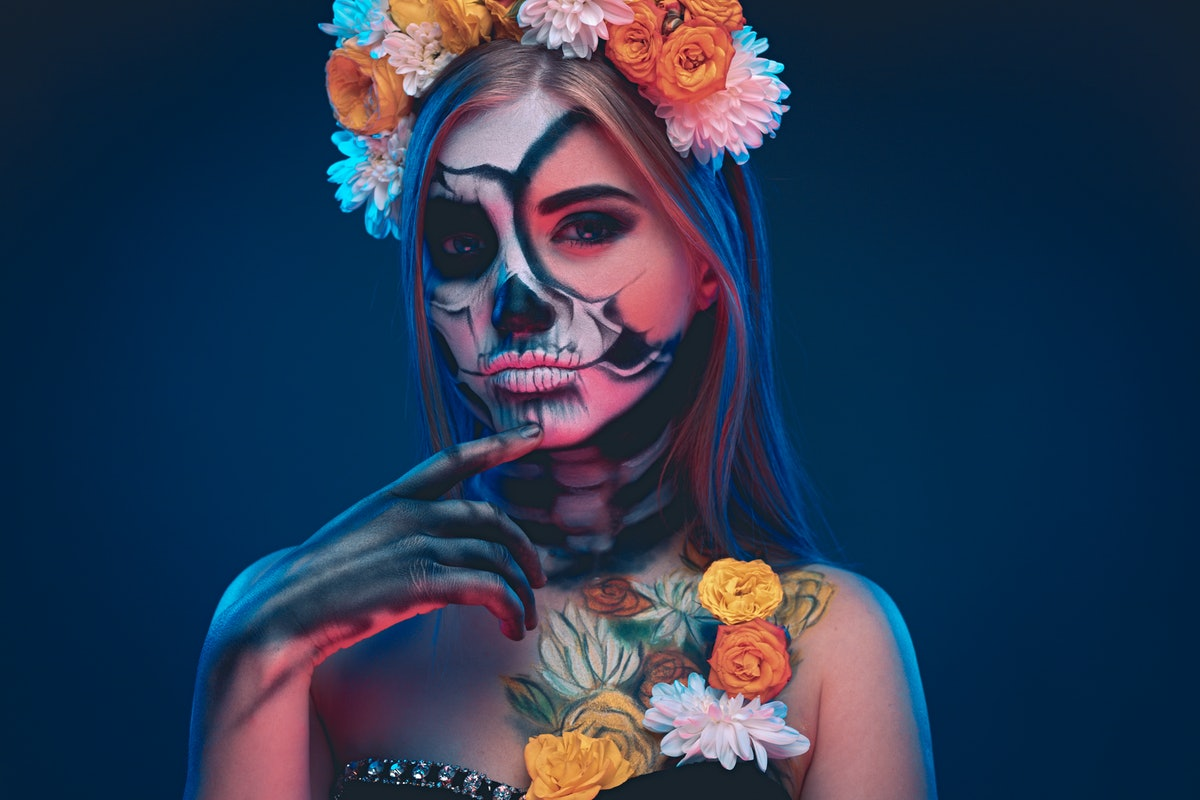 Mysterious pensive woman in floral wreath and with skull makeup poking chin and looking at camera wh...