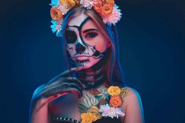Mysterious pensive woman in floral wreath and with skull makeup poking chin and looking at camera while celebrating Day of the Dead under neon light