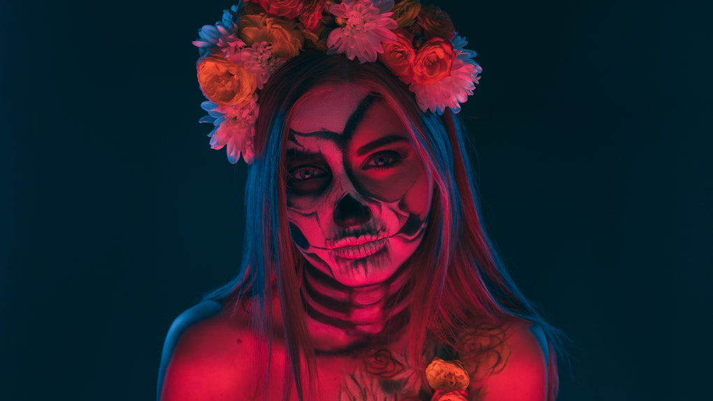 Scary lady with floral wreath and skeleton body art looking at camera during Day of the Dead carnival under red neon illumination