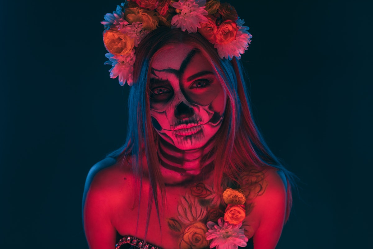 Scary lady with floral wreath and skeleton body art looking at camera during Day of the Dead carniva...