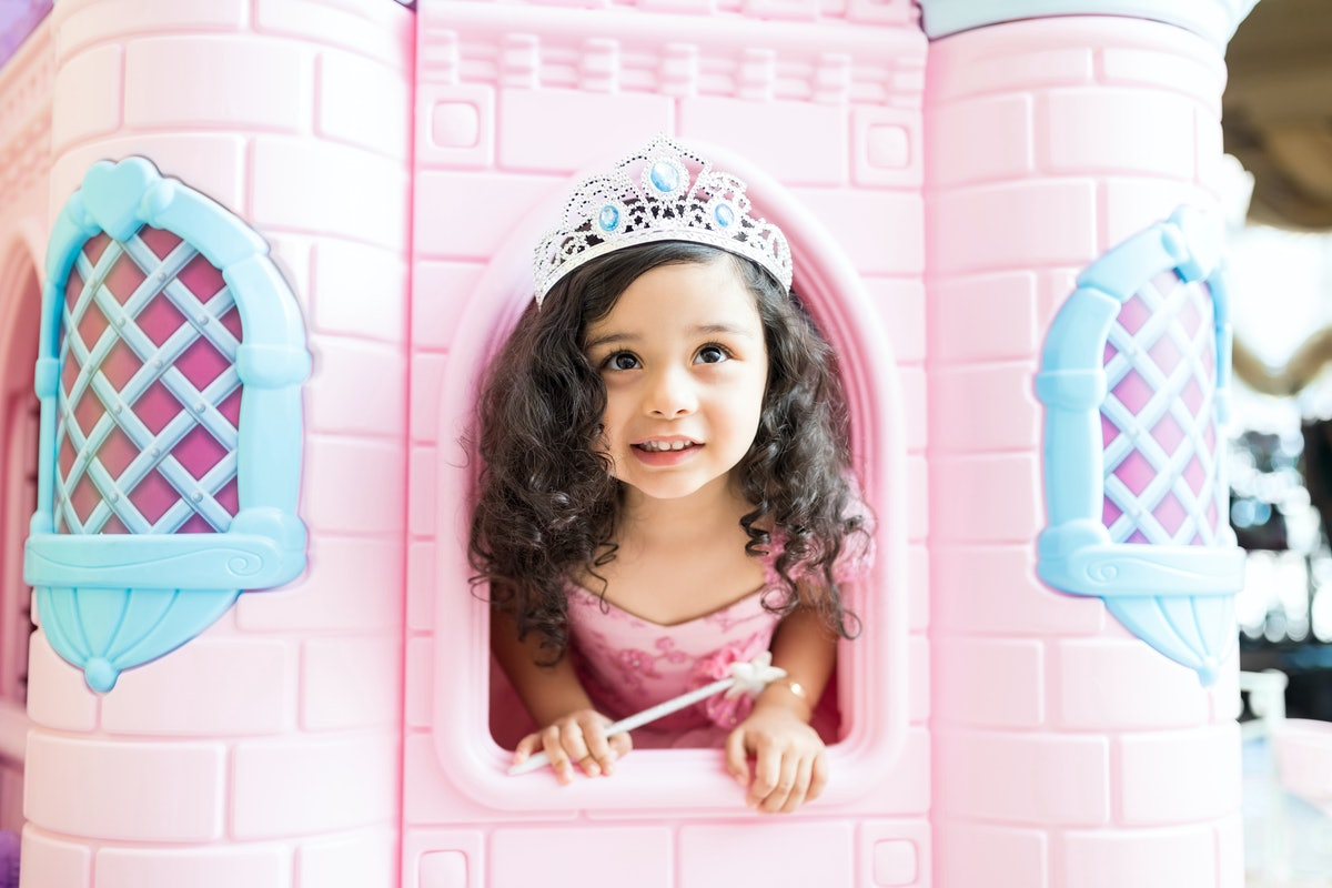 Female child wearing crown while looking through castle window at home