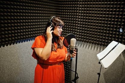 Young asian singer with microphone recording song in record music studio.