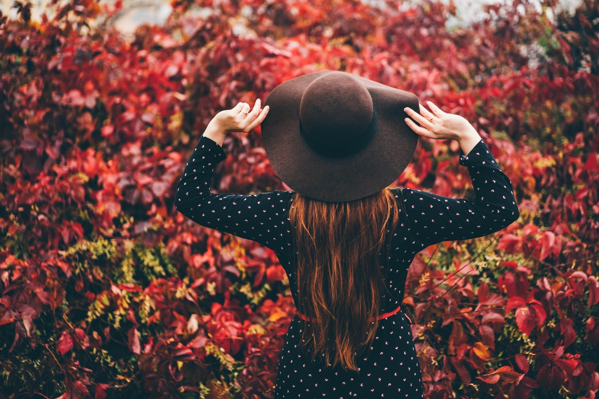 Back view of beautiful young woman in the hats standing at the autumn street. Trendy young red hair woman in fall in park. Concept of autumn mood.