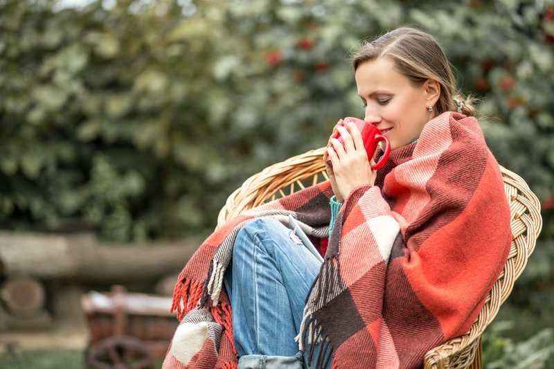 Beautiful girl resting and drinking coffee sitting in autumn garden in chair wrapped in a plaid woolen blanket. toned image