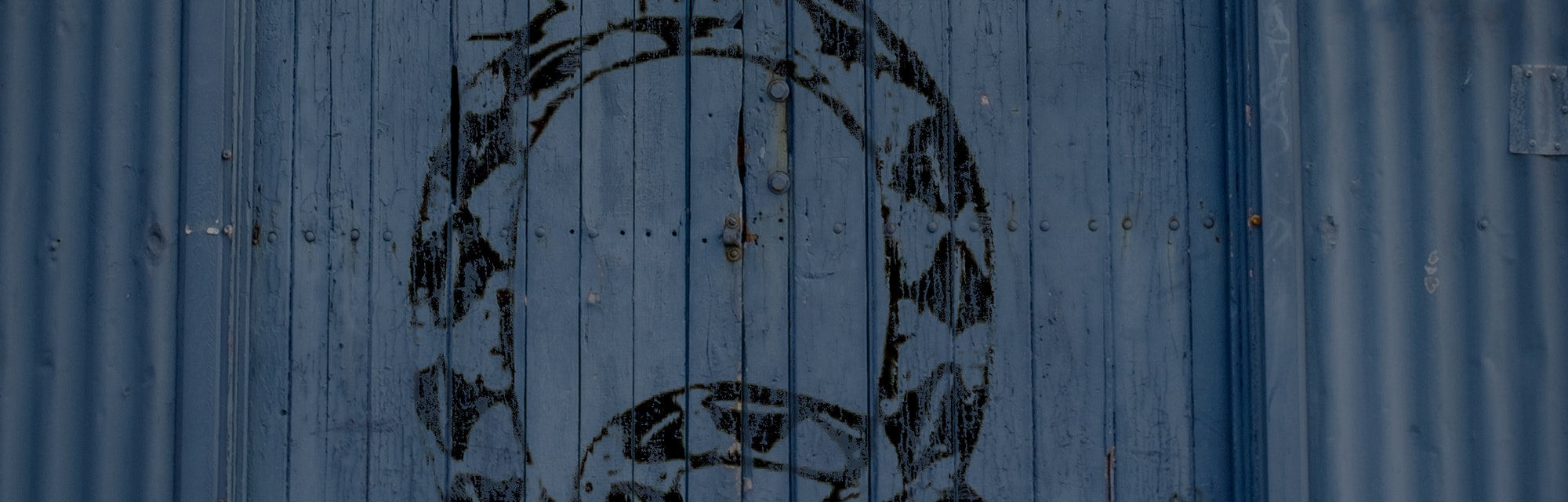 "Snake graffiti on old warehouse door which shows the conspiracy theory secret society QAnon's signature ""Q."""