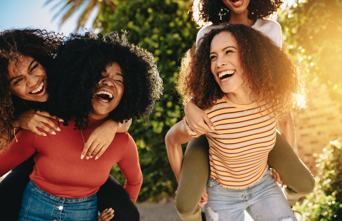 Cheerful female friends walking outdoors in city and having fun. Young women piggybacking their friends outdoors in the city.