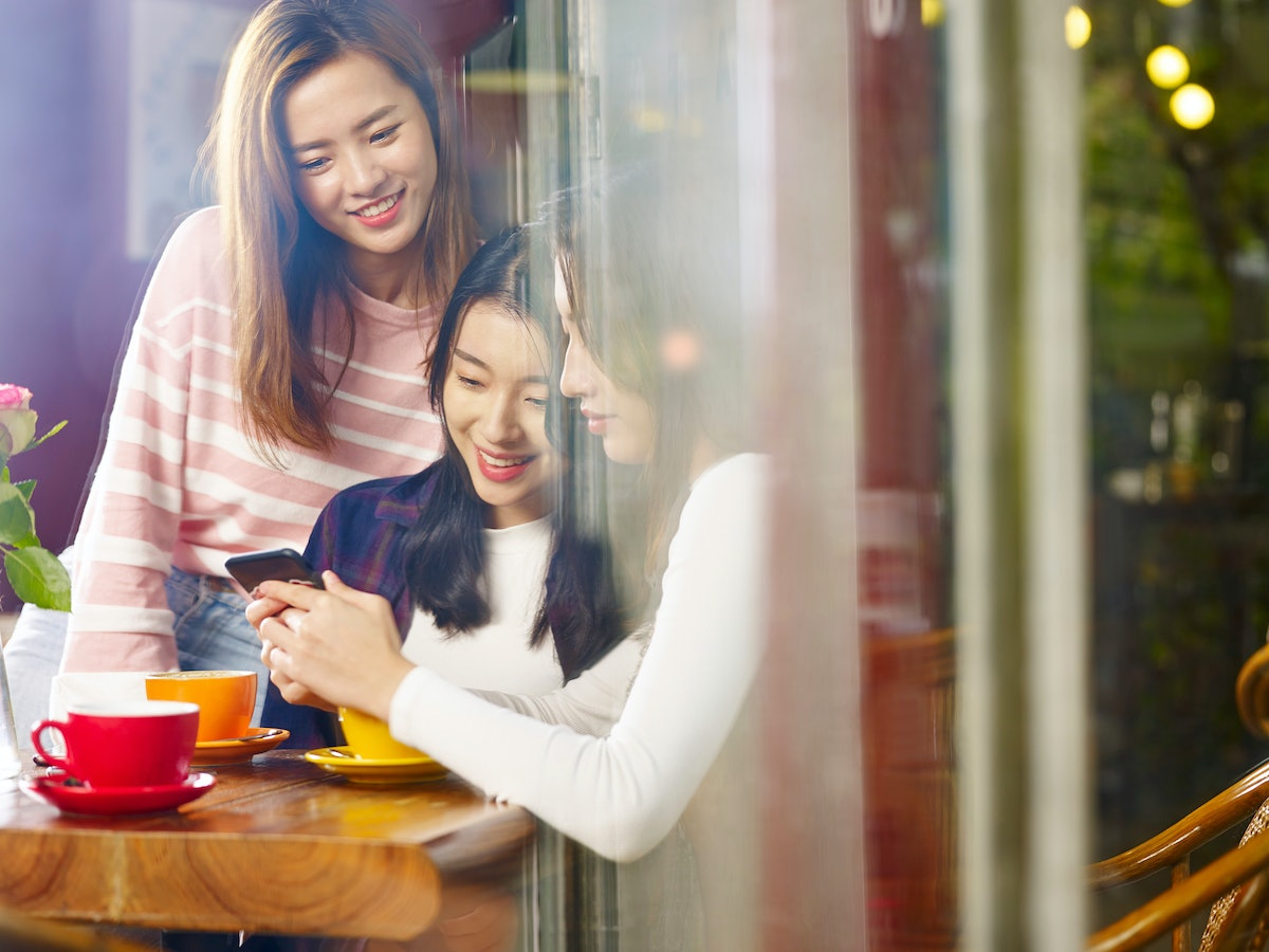 three happy beautiful young asian women sitting at table chatting talking playing with cellphone in ...
