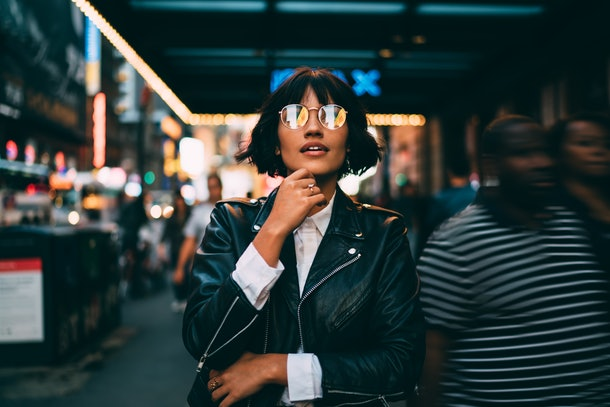 Youthful female traveller in stylish spectacles for vision correction spending time for walking around metropolitan downtown and explore New York nightlife on leisure, young woman in streetwear