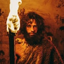 Portrait of Primeval Caveman Wearing Animal Skin Standing in His Cave At Night, Holding Torch with Fire. Primitive Neanderthal Hunter / Homo Sapiens At Night Alone. In the Background Cave Art Drawings