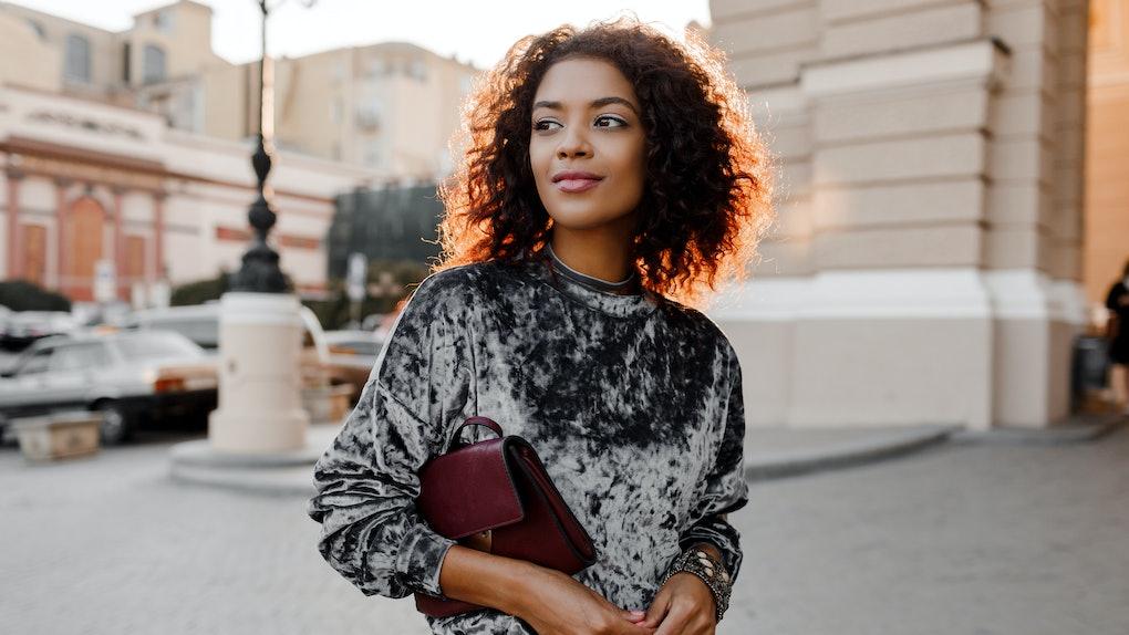 Fashionable black girl in  amazing grey velvet sweater , luxury jewelry  accessories   walking  in Paris.