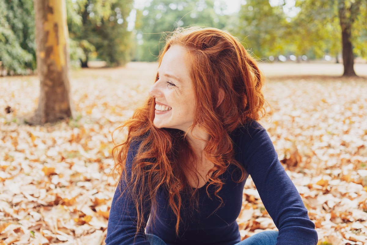 Cute happy young woman with tousled red hair relaxing in a park in autumn sitting amongst the fallen...