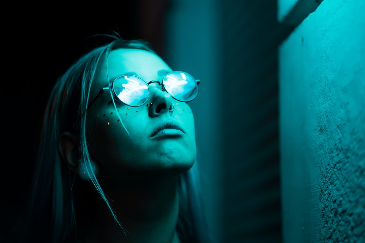 Millennial enigmatic pretty girl with unusual dyed hairstyle near glowing neon wall at night. Blue h...