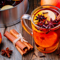 Hot mulled apple cider with with cinnamon sticks, cloves and anise on wooden background
