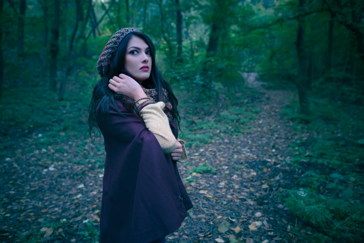 Gorgeous woman scared in autumn forest in the evening. Lonely woman in the woods. Girl running away ...