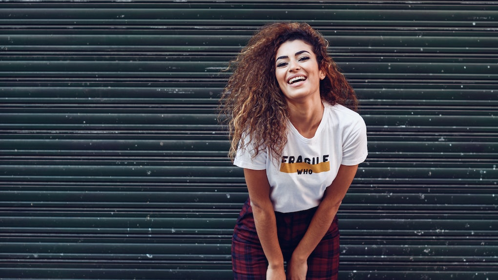 Smiling young arabic woman with black curly hairstyle. Arab girl in casual clothes in the street. Happy female wearing white t-shirt and checked pants against urban blinds.