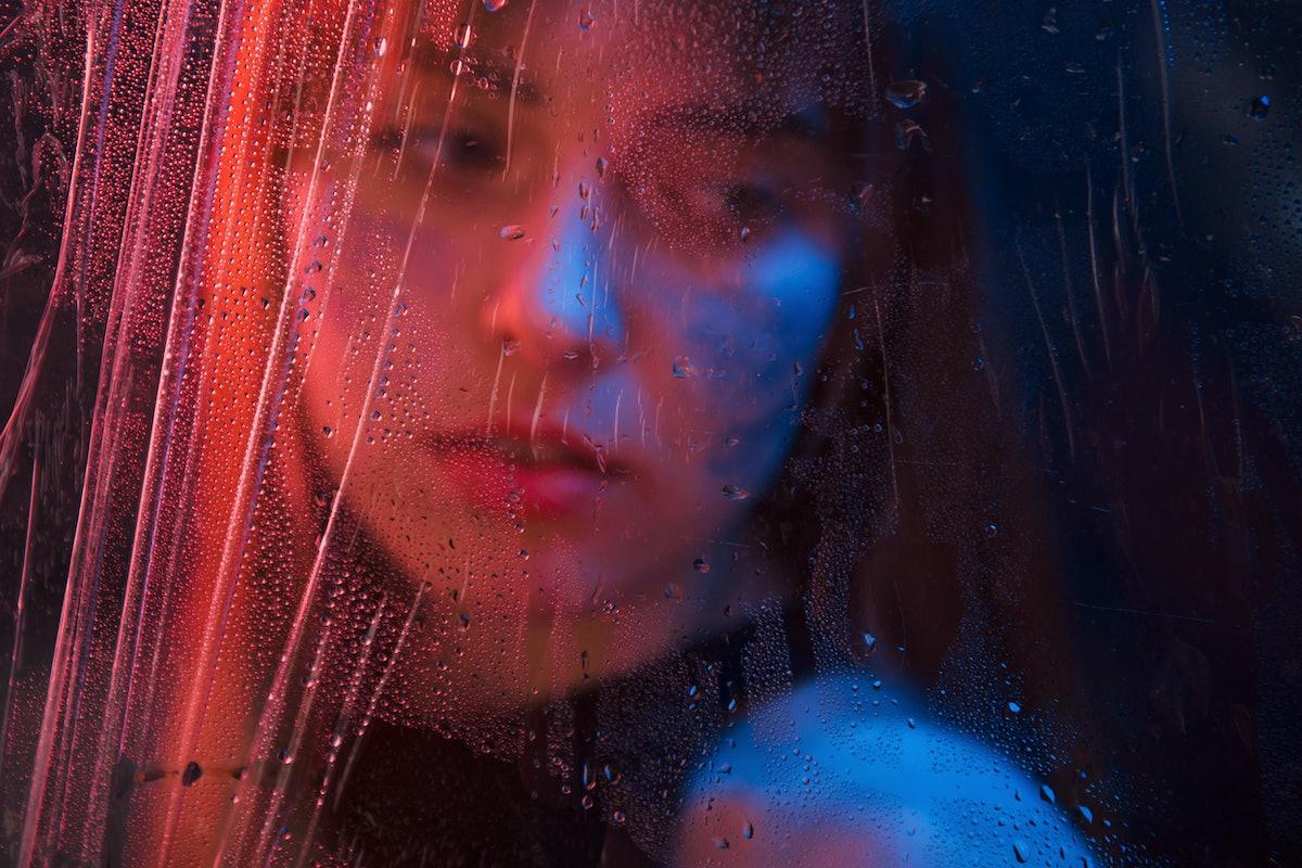 Sad woman. Studio shot in dark studio with neon light. Portrait of beautiful girl behind wet glass.