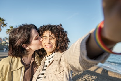 A sweet queer couple takes a kissing selfie on the beach for Instagram.