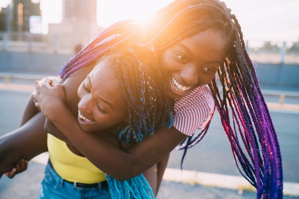 Close up two sisters outdoor back light outdoor hugging having fun - happiness, fooling around, togetherness concept