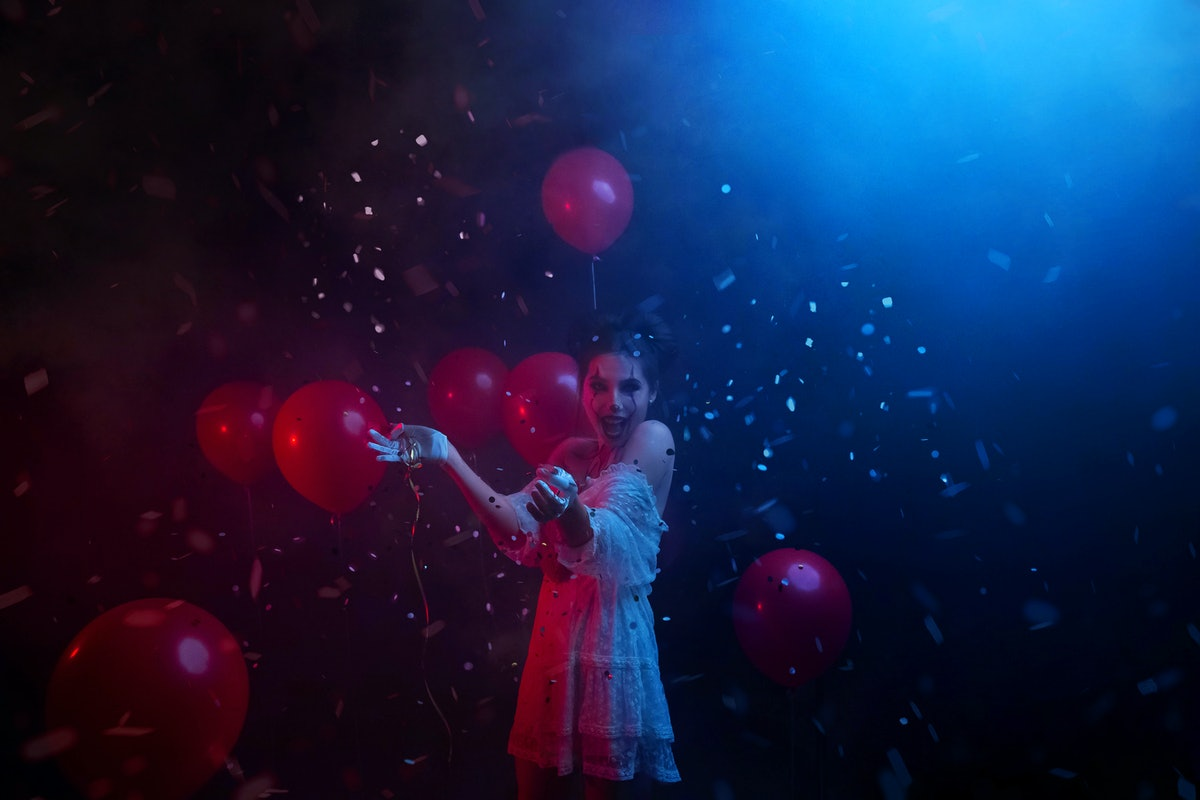 woman in clown costume laughs fun at party with neon red blue light, explodes spangles falling serpe...