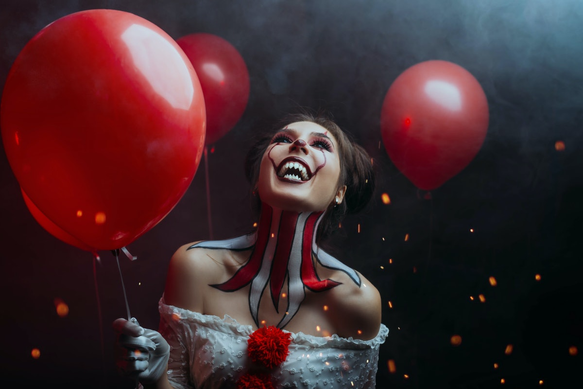 close-up portrait female clown woman scary crazy smiling laugh shows sharp teeth predator face, hold...