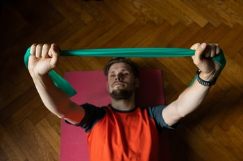 Virtual fitness training, stretching resistance bands exercises online men at home with tablet. Attractive guy lying on fitness mat online lessons blank tablet screen. Above high angle view