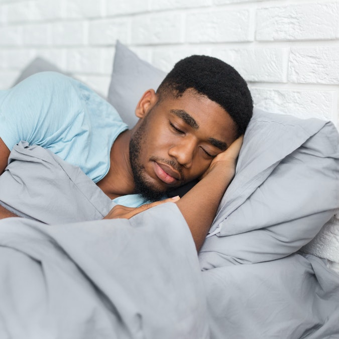 Just resting. Young african-american man sleeping in bed at home, having good dreams, copy space